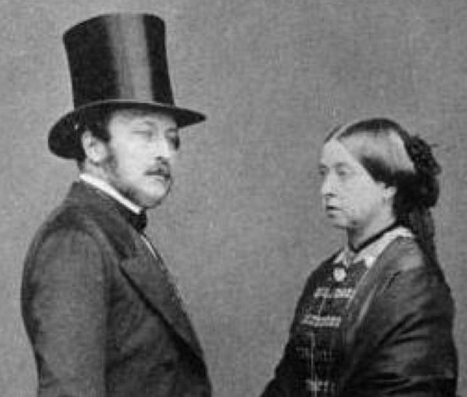 Queen Victoria looks uncertainly at her husband as Prince Albert tries out his new top hat