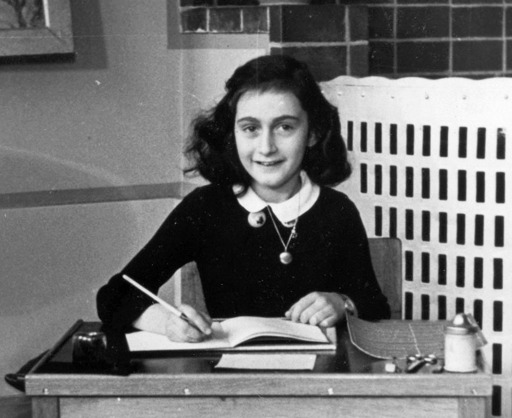 Happy Anne Frank sitting at a schooldesk in 1940, unaware of the horrors to come