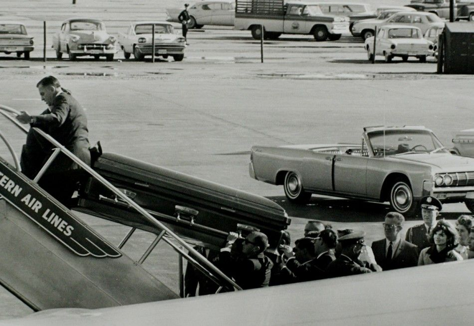 Watched by widowed First Lady Jacqueline Kennedy, the slain JFK's casket is carried aboard Air Force One for its flight from Dallas to Washington DC