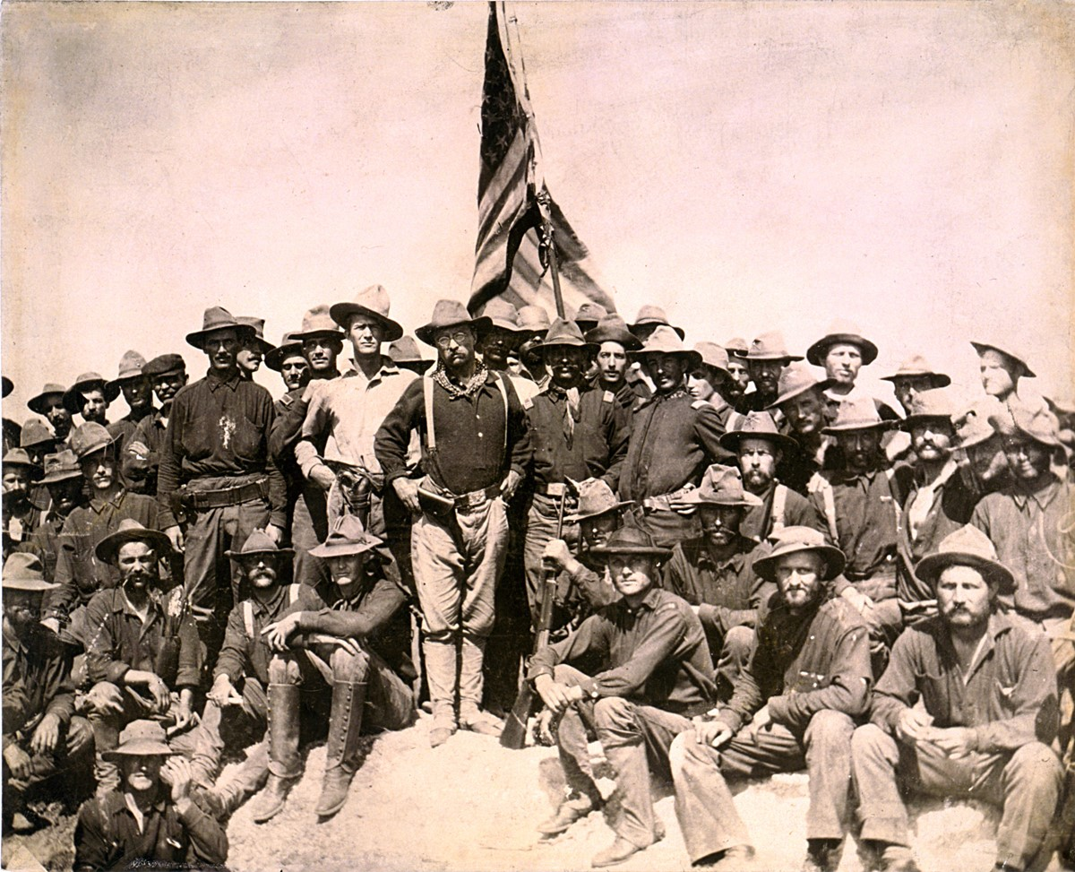 Colonel 'Teddy' Roosevelt (centre, with glasses and holstered gun) with his 'Rough Riders' after victory at the Battle of San Juan Hill.