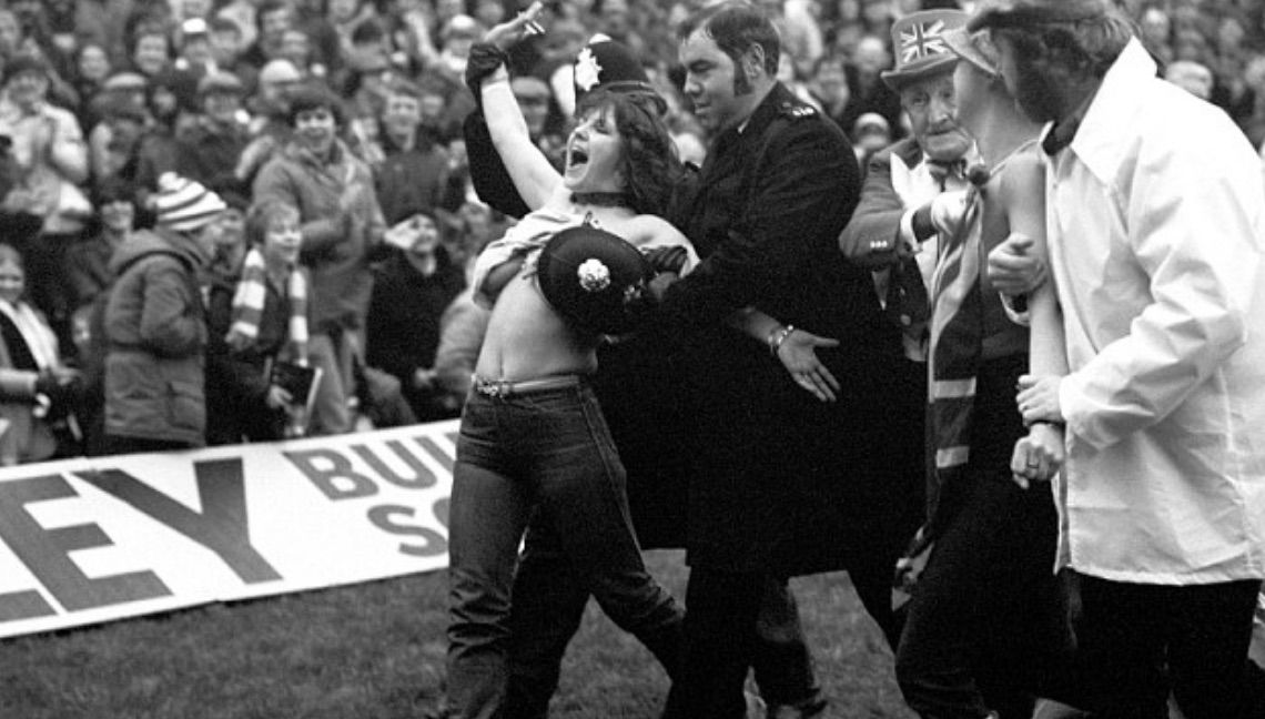 With a police helmet covering her assets, Erika Roe is escorted from the pitch. Photo: Press Association