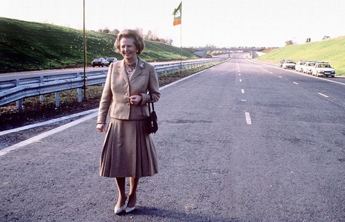 Margaret Thatcher poses on the M25 before cutting a ribbon to open it