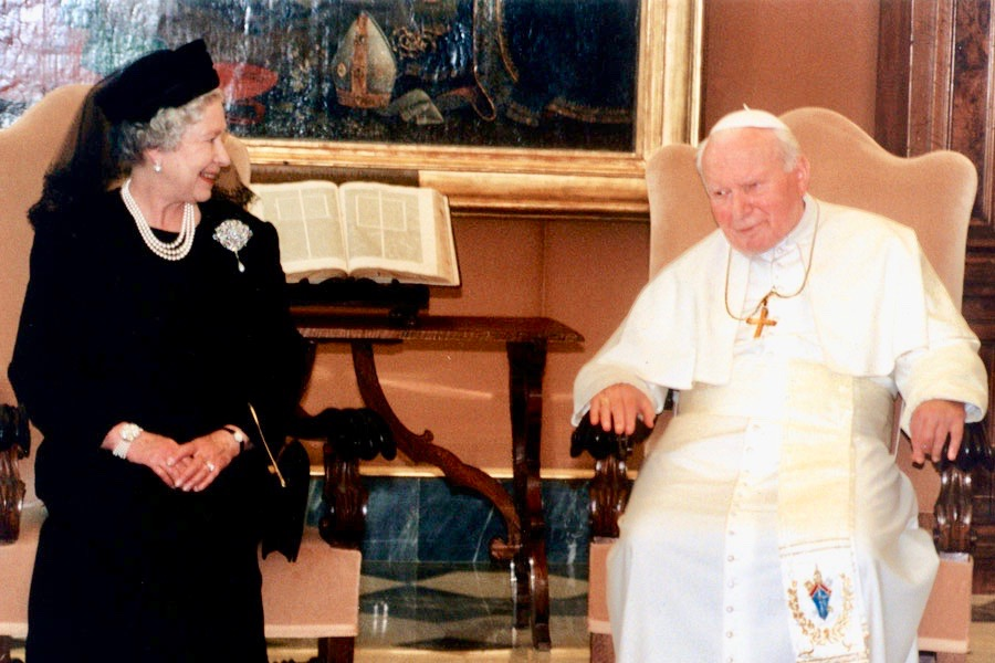 Defender of the Faith Queen Elizabeth II is all smiles at a meeting with an unhappy-looking Pope John Paul II