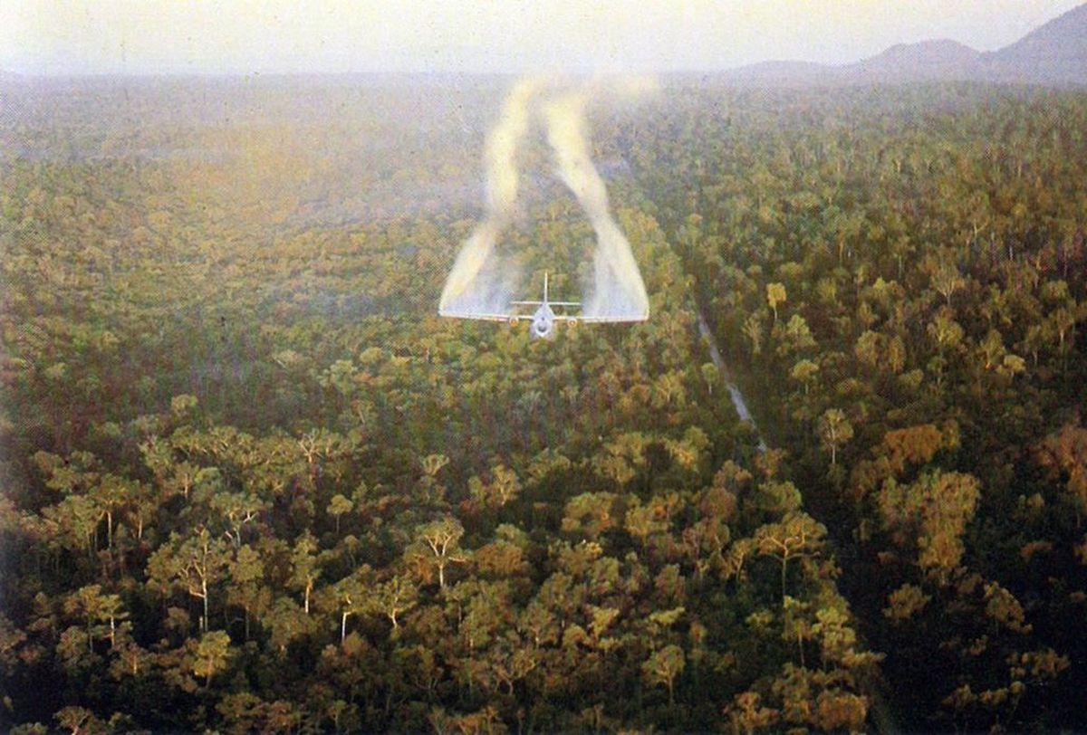 American C-123 spraying chemical defoliant, Agent Orange, on a dense Vietnamese jungle