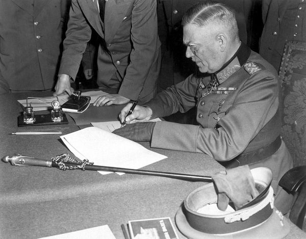 German commander Wilhelm Keitel signs the final unconditional surrender of Germany in the ruins of Berlin