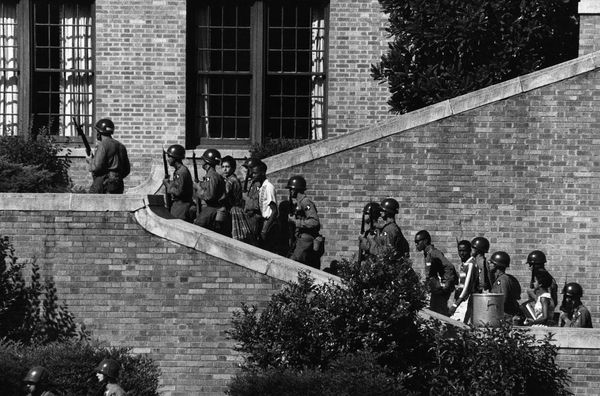 The 101st Airborne Division escort the nine black students into Little Rock School in Arkansas