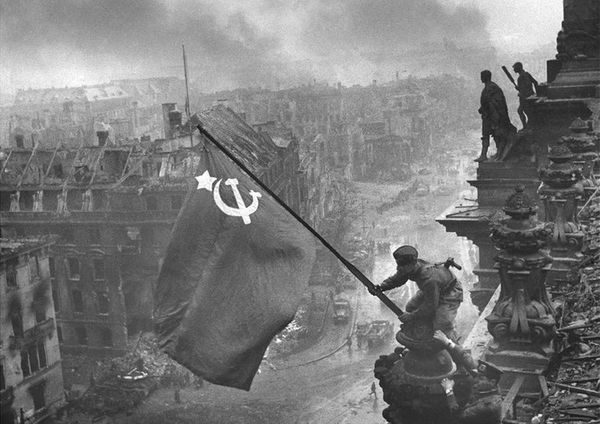 Soldiers Raqymzhan Qoshqarbaev and Georgij Bulatov raise the Soviet Union flag on the roof of the Reichstag building in Berlin