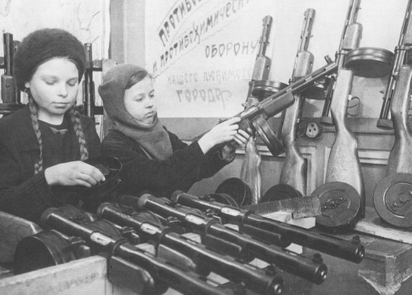 Two young girls help assemble Soviet submachine guns during the Siege of Leningrad