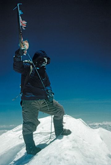 Tenzing Norgay brandishes his ice axe on the summit of Mount Everest
