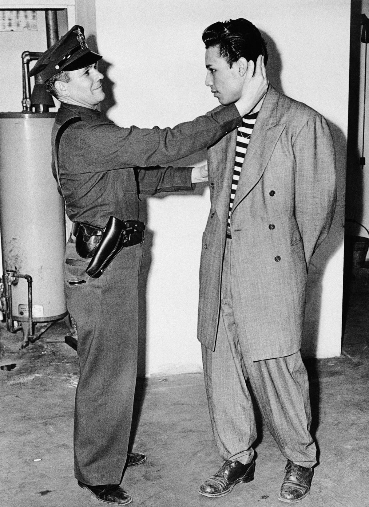 A man in a zoot suit is inspected after being arrested by the LAPD in 1943